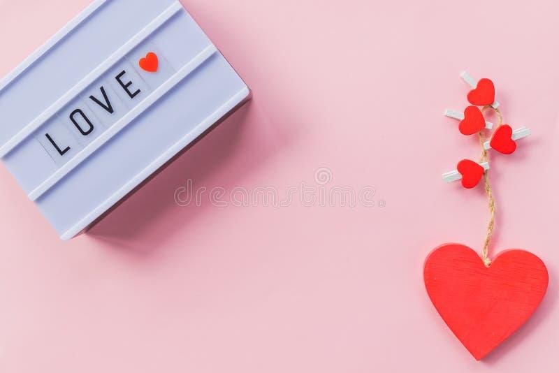 Любовь слово написана на светлой коробке белизна розы красного цвета лепестков влюбленности надписи Украшение на свадебный банкет стоковая фотография