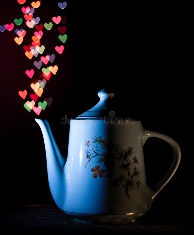 Любовь сформировала bokeh от античного керамического чайника стоковое изображение rf