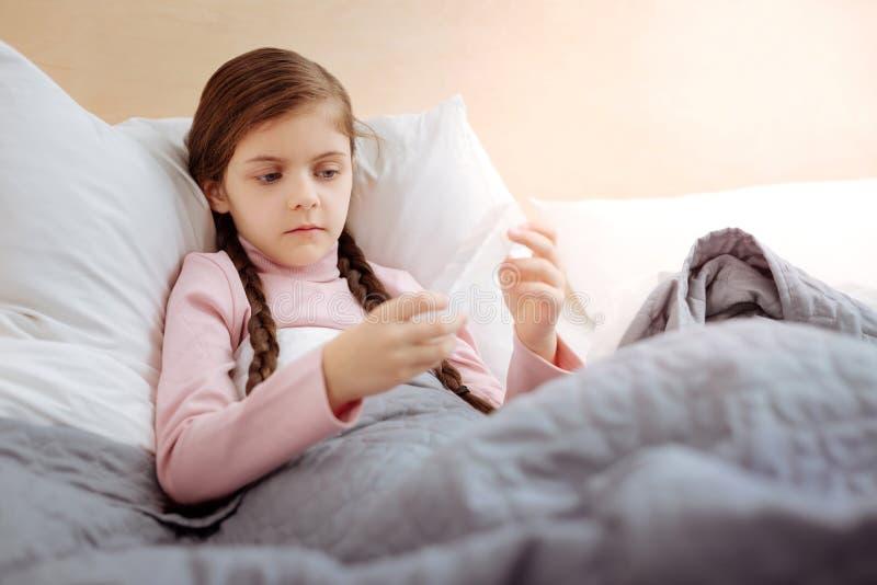 Любознательная девушка держа маленькую коробочку для таблеток стоковое фото