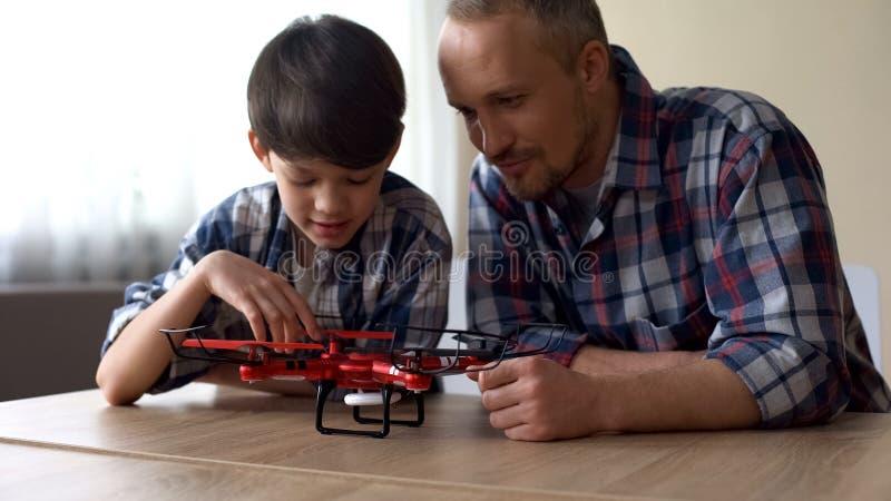 Любознательный отец и маленький сын рассматривая новую модель quadrocopter дома, потеха стоковое изображение