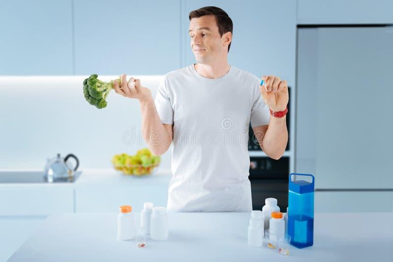 Любознательный человек усмехаясь пока выбирающ между принимать пилюльку и едой брокколи стоковые изображения rf
