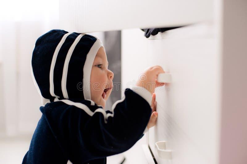 Любознательный младенец раскрывает шкаф стоковое изображение