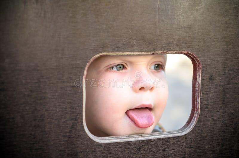 Любознательный ребенк шпионя через отверстие в деревянной стене на спортивной площадке стоковое фото rf