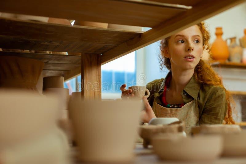 Любопытная длинн-с волосами курчавая девушка смотря вне для воодушевленности стоковая фотография rf