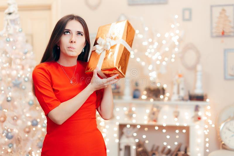 Любопытная женщина проверяя подарок рождества в утре стоковая фотография rf