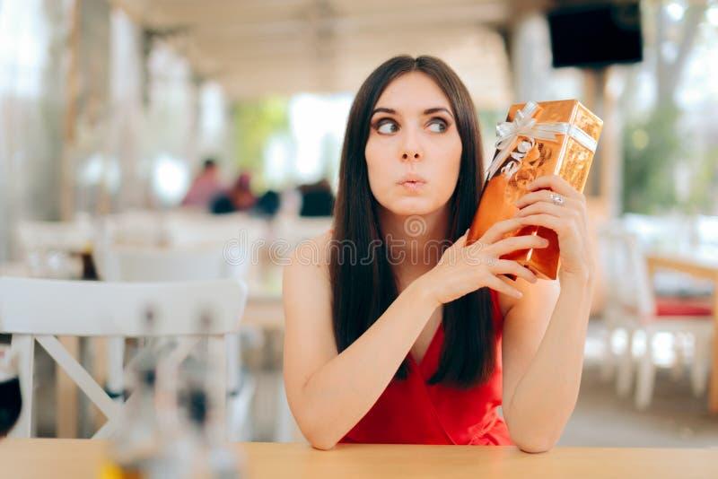 Любопытная женщина проверяя подарочную коробку на дате стоковая фотография