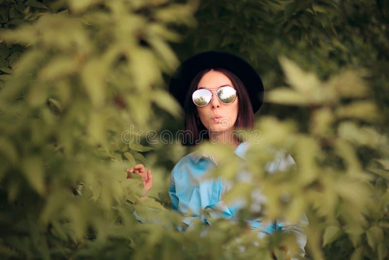 Любопытная ревнивая женщина шпионя от кустов стоковые фотографии rf