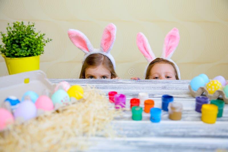 Любопытные небольшие девушки в ушах зайчика peeking вне от заднего кухонного стола с вкусными пасхальными яйцами и смотря камеру стоковое изображение
