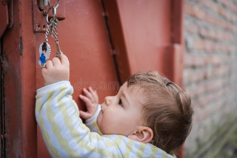Любопытный ребенок играя с ключами outdoors стоковое фото