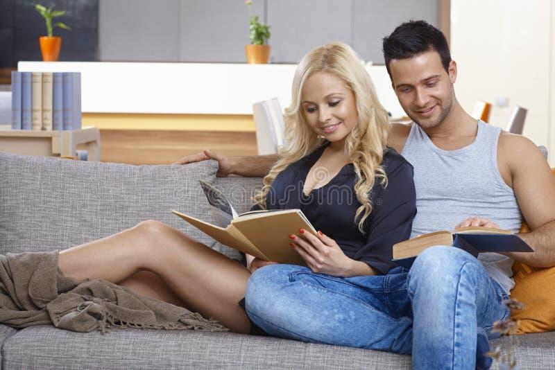 Любящая книга чтения пар на софе стоковая фотография