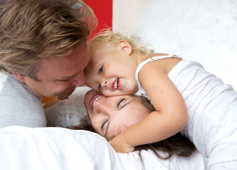 Любящая мать и отец усмехаясь с маленьким ребенком стоковое фото