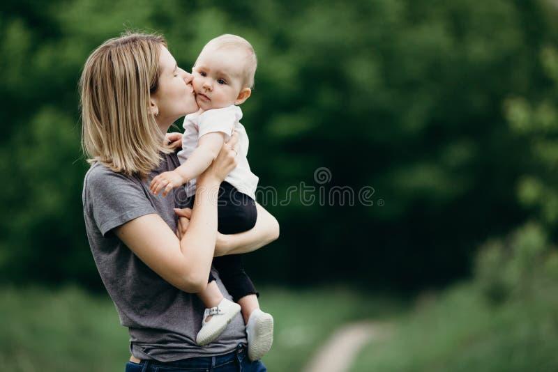 Любящая мать целуя ее дочь младенца outdoors стоковые фото