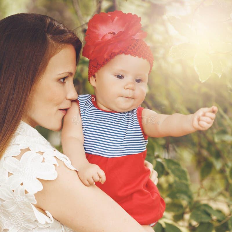 Любящая молодая мать держа и целуя ее младенца стоковое фото rf