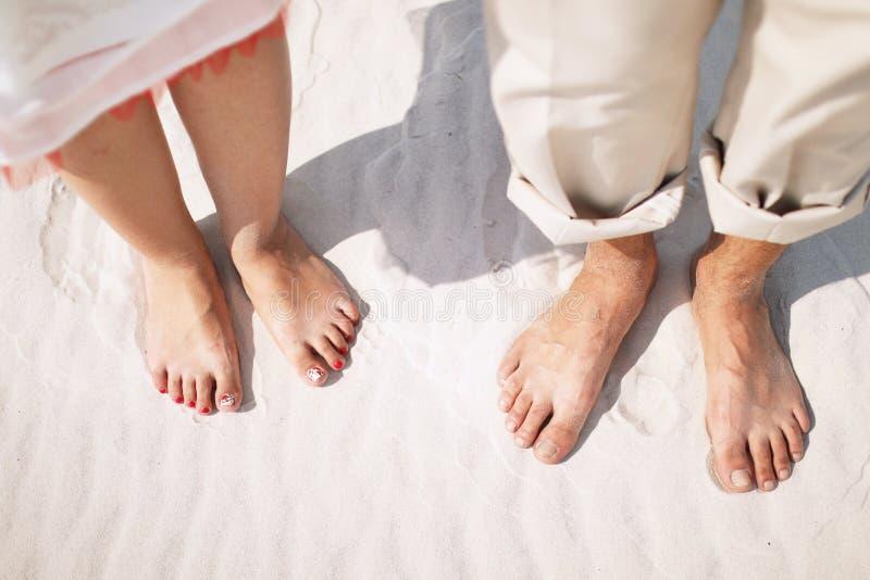 Любящая пара в жилетах и босоногие стойки на береге озера стоковые изображения rf
