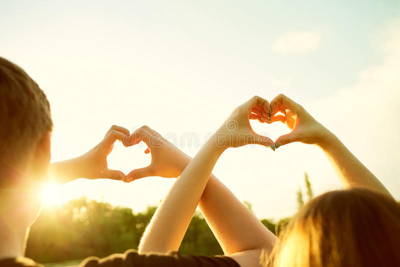 Любящая пара делает символ силуэта сердца влюбленности с их стоковое фото