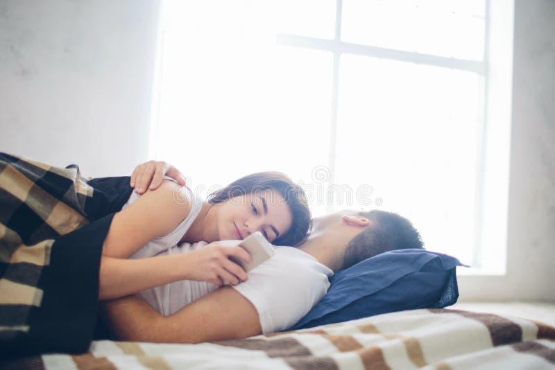 Любящая пара arelying на кровати Женщина использует smartphone стоковое изображение