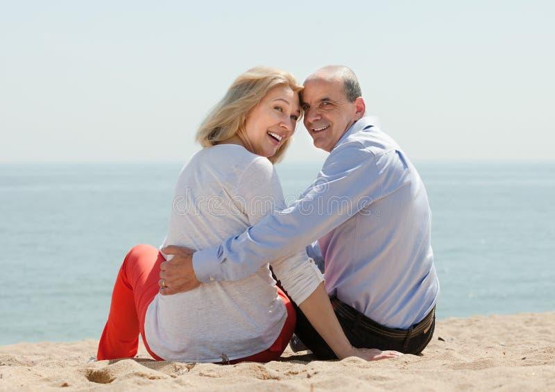 Любящие зрелые пары на пляже песка стоковое фото rf