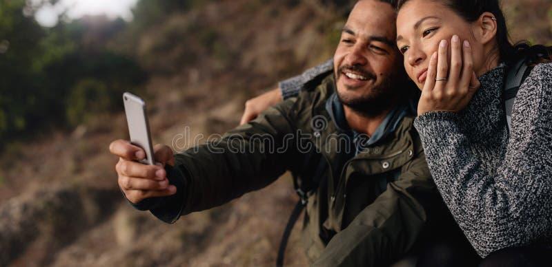 Любящие молодые пары на походе принимая selfie стоковое изображение