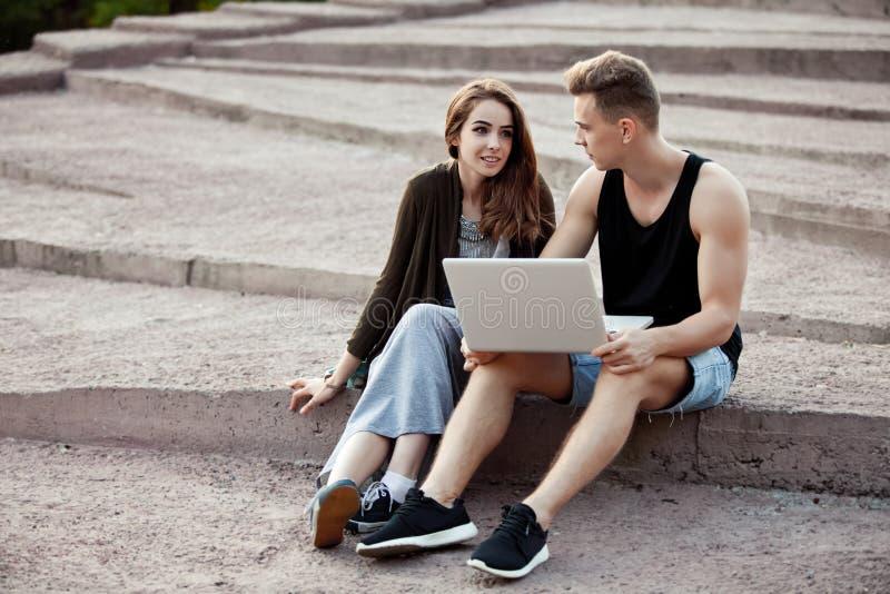 Любящие молодые пары сидя на прогулке с компьтер-книжкой стоковая фотография rf
