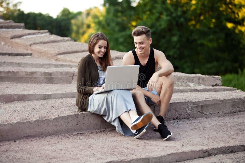 Любящие молодые пары сидя на прогулке с компьтер-книжкой стоковые фото