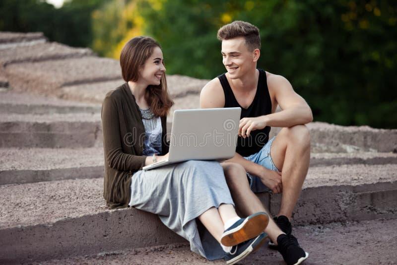Любящие молодые пары сидя на прогулке с компьтер-книжкой стоковые изображения rf