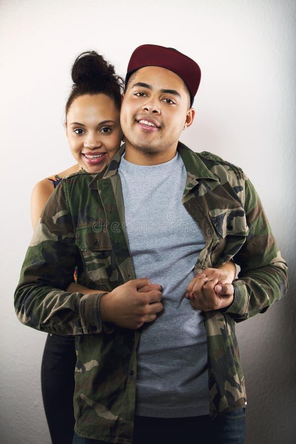 Любящие молодые пары совместно на серой предпосылке стоковая фотография rf