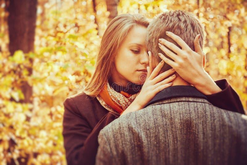 Любящие пары в осени паркуют на солнечном дне стоковые изображения rf