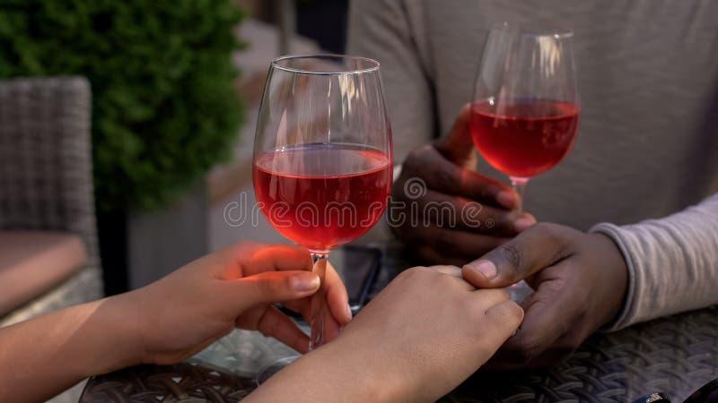 Любящие пары держа руки ослабляя в кафе с бокалами на таблице, дате стоковые изображения rf