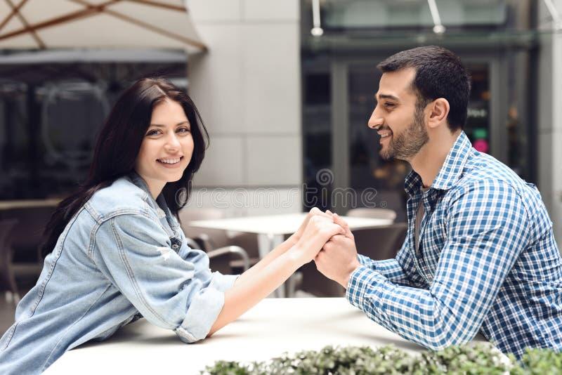 Любящие пары держа руки сидя на таблице в кафе стоковые фотографии rf