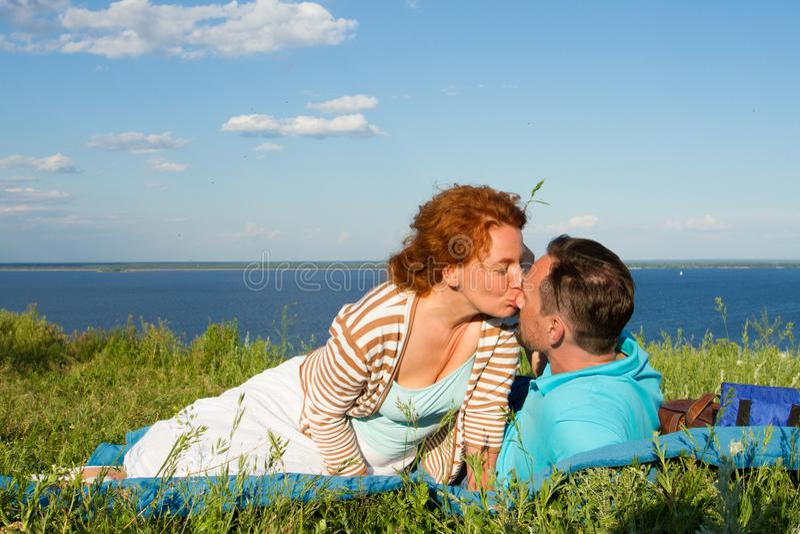 Любящие пары людей сидят на земле Парень и девушка на одине другого захода солнца целуя в облаках с небом стоковая фотография rf