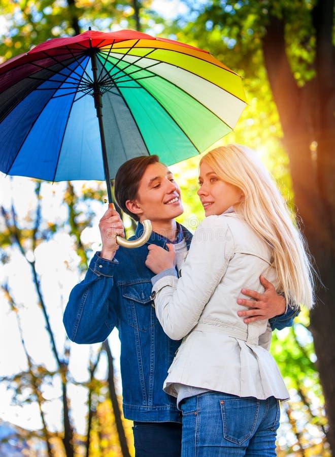 Любящие пары на дате под зонтиком Через Солнце после дождя стоковые фотографии rf