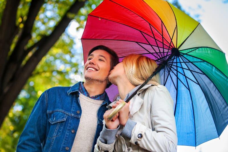Любящие пары на романтичной дате под зонтиком осени стоковые фотографии rf