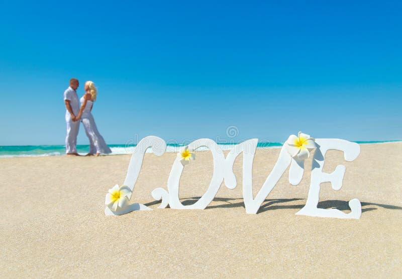 Любящие пары на тропическом песчаном пляже океана с влюбленностью формулируют оформление стоковая фотография