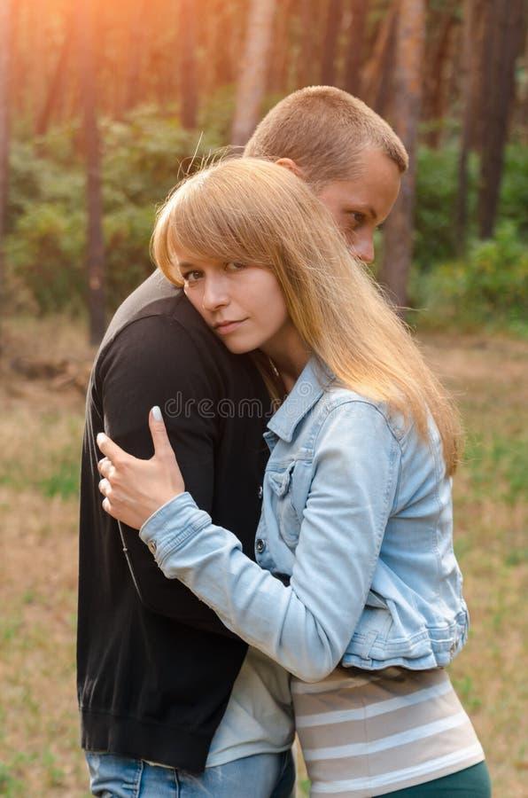 Любящие пары обнимая один другого outdoors, лес стоковые изображения