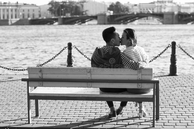 Любящие пары сидя на стенде и целовать стоковые фотографии rf