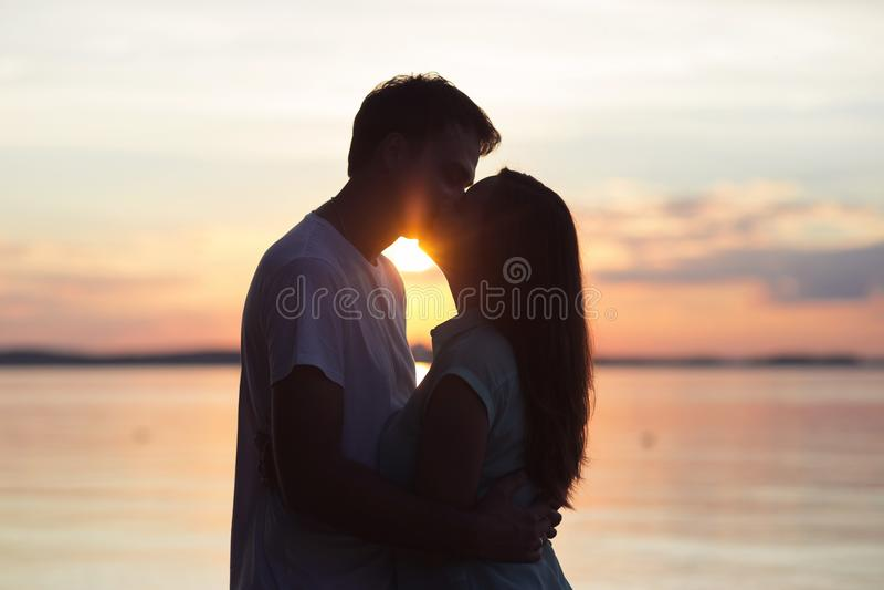 Любящие пары целуя на заходе солнца Влюбленность в солнце День ` s валентинки в природе стоковые изображения rf