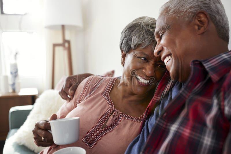 Любящие старшие пары сидя на софе дома ослабляя с горячим питьем стоковые фото