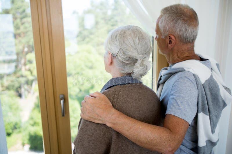 Любящие старшие пары смотря окно стоковая фотография rf