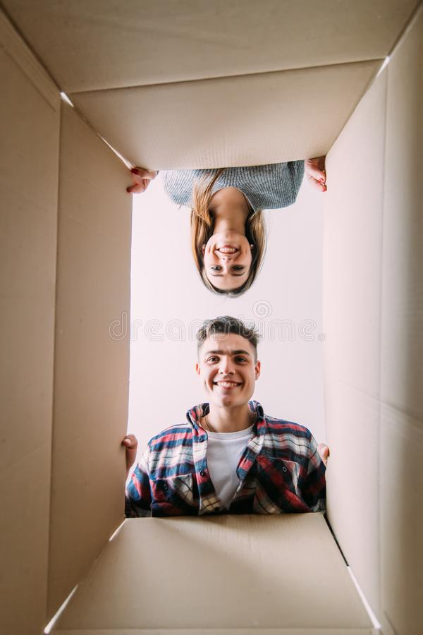 Любящие человек и женщина смотрят в коробках для двигать Взгляд изнутри коробки стоковая фотография