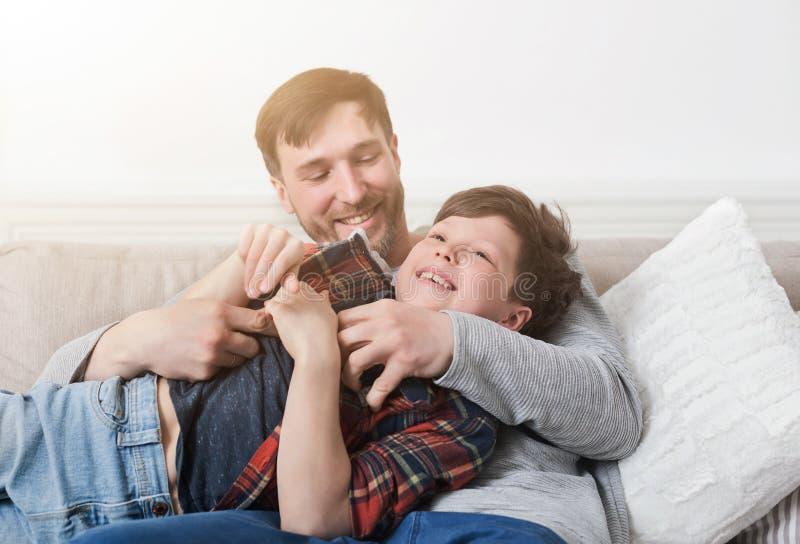 Любящий отец имея потеху с его сыном на софе стоковые фото