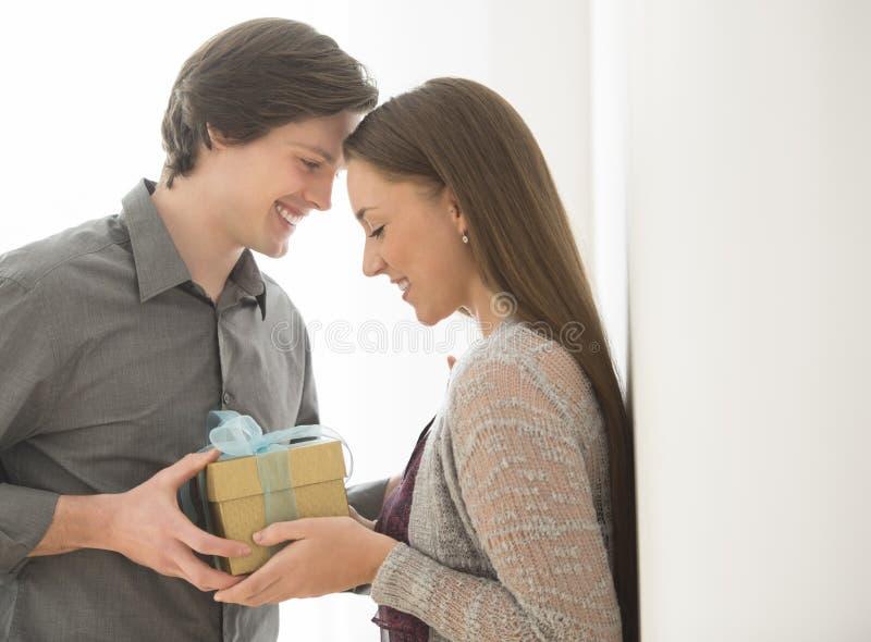 Любящий человек давая подарок на день рождения к женщине стоковые изображения