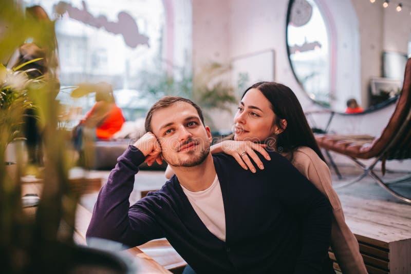Любя девушка держит ее руку на плече ее парня сидя на таблице в уютном романтичном кафе стоковое изображение rf