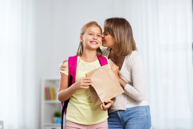 Любя мать давая школьный обед дочери дома стоковые фото