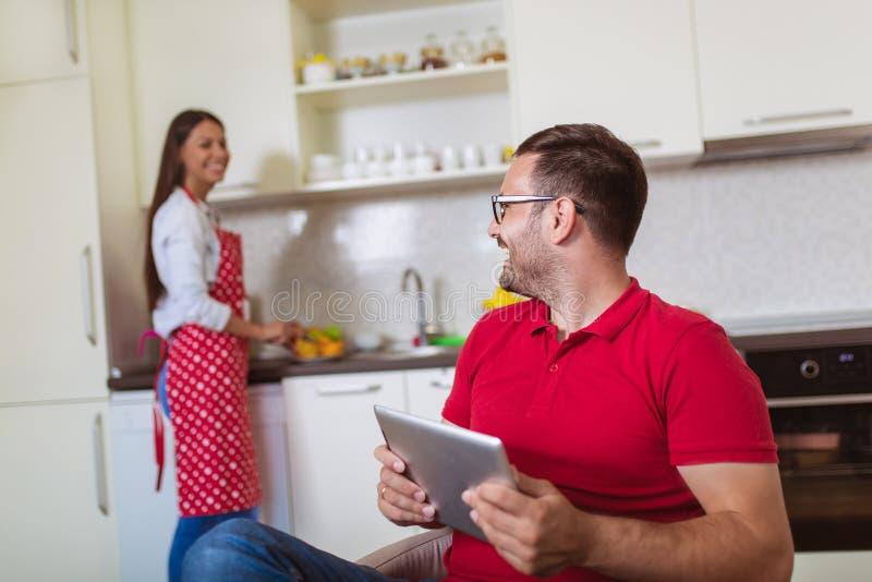 Любя молодые пары в кухне в утре Человек используя цифровой планшет стоковая фотография rf