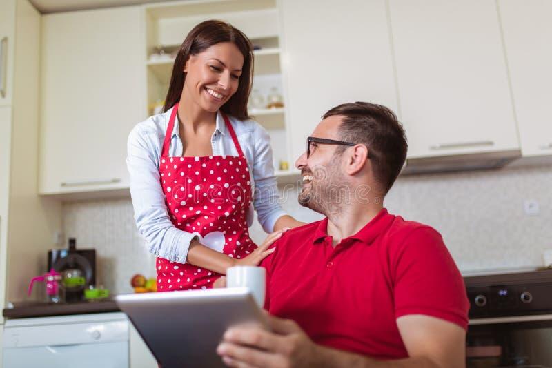 Любя молодые пары в кухне в утре Человек используя цифровой планшет стоковое фото rf