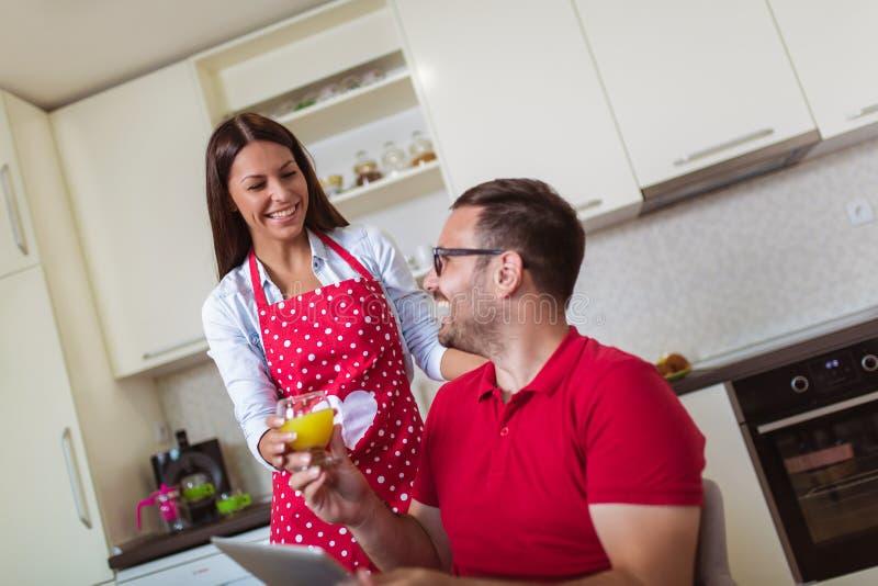 Любя молодые пары в кухне в утре Человек используя цифровой планшет стоковое фото