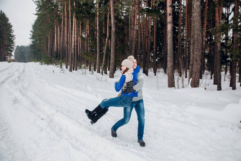 Любя молодые пары имея потеху в лесе зимы стоковое изображение