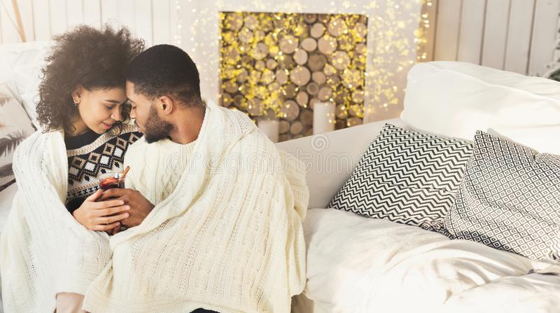 Любя обдумывать-вино Афро-американских пар выпивая в уютной комнате стоковые фотографии rf