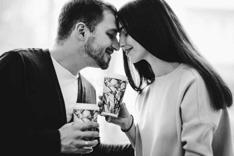 Любя пара распологает лицом к лицу на предпосылку окна и удержания чашек в их руках r стоковые фотографии rf