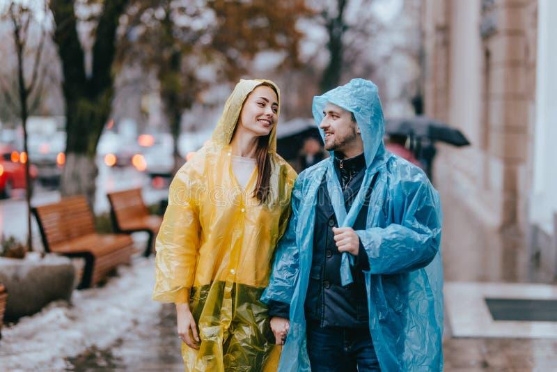Любя парень и девушка в желтых и голубых плащах идут на улицу в дожде стоковая фотография rf
